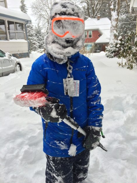 One way to keep kids occupied is to assign them tasks such as clearing vehicles of snow, as this 9-year-old is doing.