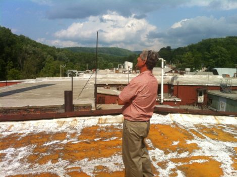 Architect Doug Brown on the roof of the Smith Mill complex looking toward Lenoxdale. The roof is visibly deteriorating and the footing is a bit tricky. Photo: Daniel Bellow