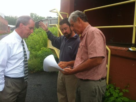 Douglas L. Brown, AIA, shows state Rep. William Smitty Pignatelli and William Powers from Congressman Richard Neal's office the plans for Smith Mill redevelopment. The narrow street behind them is an obstacle to the site's development, plans call for demolition of the buildings in the background.  Photo: Daniel Bellow