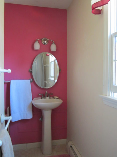 A powder room made to fit in a tiny L-shaped space.
