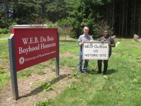 UMass anthropology Professor Robert Paynter, who has led archaeological digs at the Du Bois/Burghardt site, and Felicia Jamison, a UMass doctoral candidate, earlier this summer hold the original wooden sign that was installed at the park. The sign is now in the archive at the Du Bois Library at UMass. Photo: Bernard A. Drew