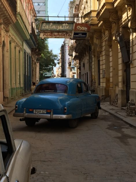 A narrow street in Havana, with cars dating from the 1950s (like the blue Chevrolet).