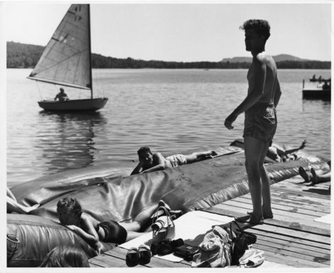 Lukas Foss stands on the pier at the Stockbridge Bowl while Tanglewood students sun themselves and a sailboard approaches in the distance. Photo: Courtesy of the Boston Symphony Orchestra