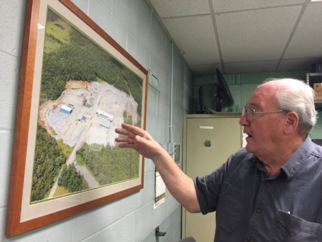 Ed Williams in his office, gesturing to an aerial view of the Williams Stone operations.