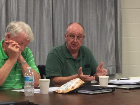 Chareles Flynn, left, listens as Dick Sears explains how the assessment error was discovered.