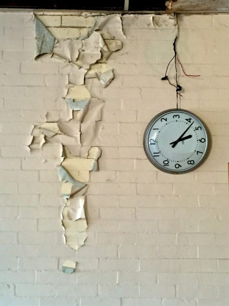 In a derelict classroom in the current school building, a clock dangles from its moorings.