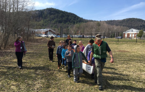 Alsop and his student crew guide his canoe down the path to Muddy Brook, with Monument Mountain in the background. Photo: David Scribner