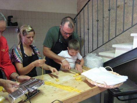The author, at right, with son Henry, cutting pasta during a cooking class in Tuscany.