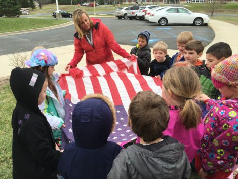 With the assistance of Amy Salinetti, her kindergarten class folds old flag that has been removed from the school's flag pole.