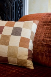The burnt orange armchair looks great with a custom checked pillow in neutral colors.