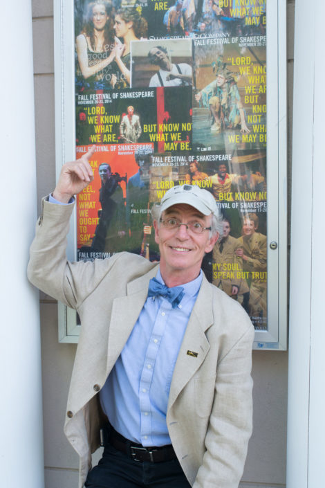 Coleman, with his signature bowtie, in front of a poster depicting the student Shakespeare festival.