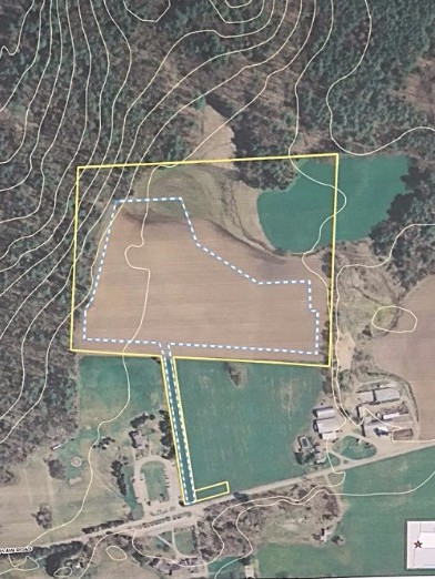 The solar array will fit inside the blue and white lines, a 10- to 12-acre parcel. The access road can be seen running alongside the playground and parking lot. It divides the Coons' land, right, from the school soccer field, left.