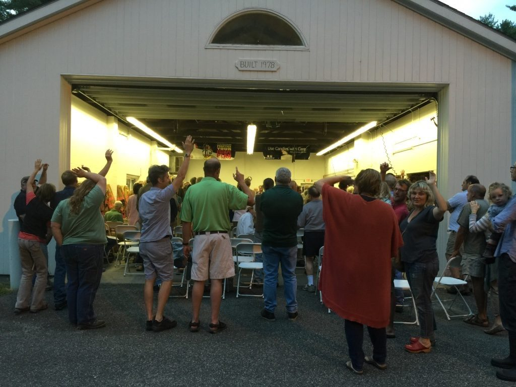 At a jam-packed August 2015 special town meeting at the Alford firehouse, voters, some of whom spilled out into the open air, stand and raise their hands to indicate support for a town-wide Internet network to provide phone service and broadband connectivity. Photo: Heather Bellow