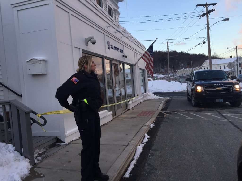 A police officer guards the crime scene at Salisbury Bank and Trust Company Monday evening after Sheridan allegedly passed the teller a note and escaped with a small amount of cash. Photo: Heather Bellow