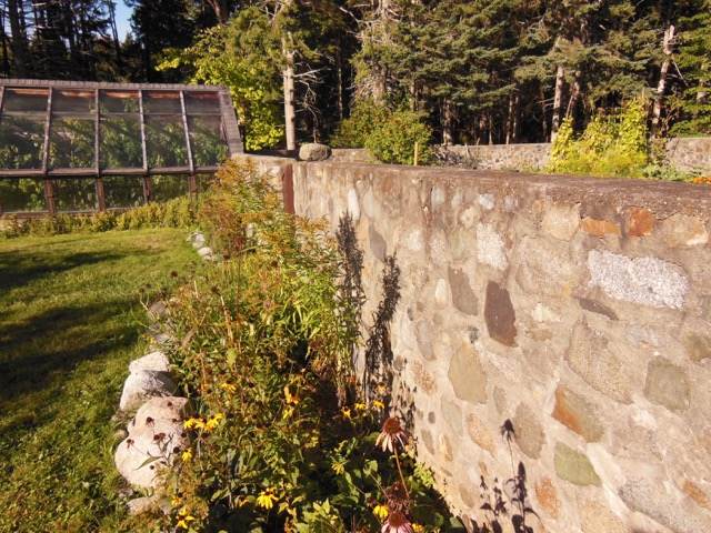 Greenhouse beside garden. Notice herb border along wall. Look over the foreground wall to the opposite perimeter wall. Photo: Mackenzie Waggaman