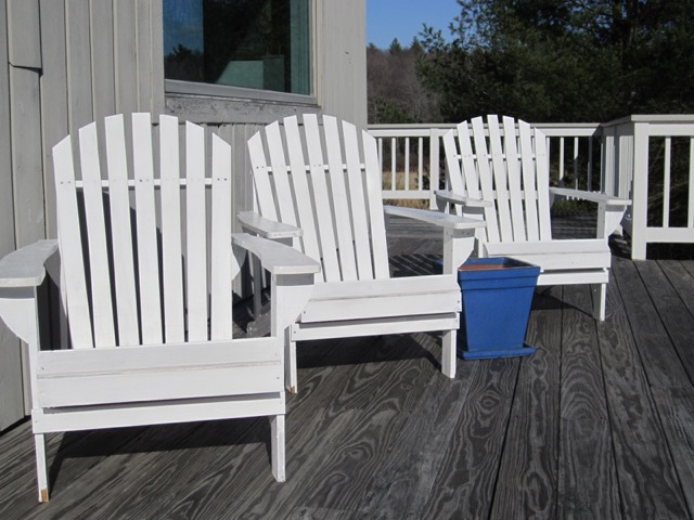 The single bright blue planter (waiting for the growing season) catches your attention among the bright white Adirondack chairs on this deck in Sandisfield.