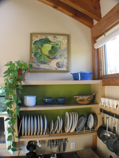 """""""Forest Moss"""" is used behind the open dish selves here in a kitchen in Egremont. The walls are """"Yellow Squash"""" and the trim is """"Acorn Yellow"""". The oil painting is by Kate Knapp."""