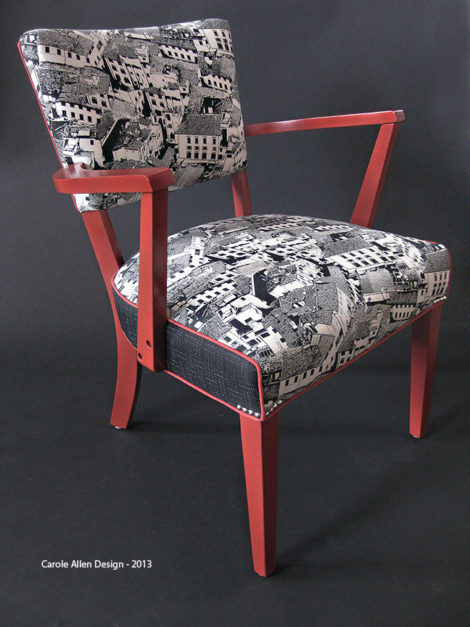 """The black and white fabric print of Florence rooftops by Carole Allen Design is accented with piping, the color of which is picked up on the frame of this simple chair. Before upholstering the chair was painted with Liquitex professional spray, """"Cadmium Red Light"""" Hue 2, then coated with a satin clear spray finish."""