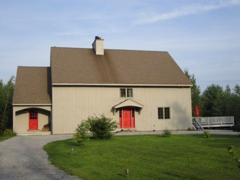 """This large barn-like post and beam home in Sandisfield is oriented to the natural setting out back and to the side. The view from the road where one approaches would seem austere without the bright red doors which give a mere hint of the stylish and unique interior. Exterior stain, """"Seagull Grey,"""" doors """"Bonfire."""""""