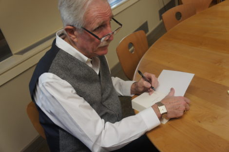 Author Harry MacLean inscribes one of his books. Photo; Hannah Barrett
