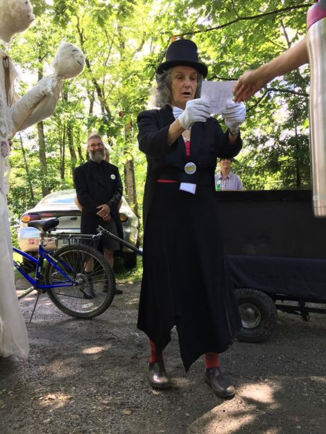 'Funeral director' Linda Putnam pauses to read before casting into the 'coffin' a sheet of paper depicting a 'dead' issue. Photo: Sugar Shack Alliance