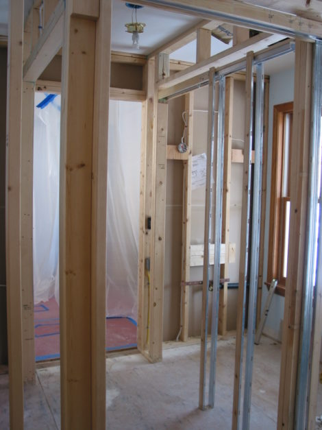 This view during construction looks toward the entry where the plastic hangs. On the right is the framing for the new powder room while the frame for the closet opening is on the left. - Photo Credit: Erica Fay