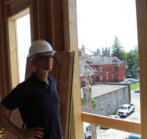 Sam Nickerson at a window overlooking the Castle Street Firehouse annex, with Town Hall beyond. Photo: Terry Cowgill