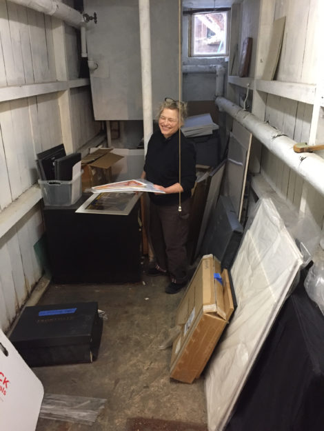 Carolyn sorting and cleaning art in a basement store room. Photo: Eli Newberger